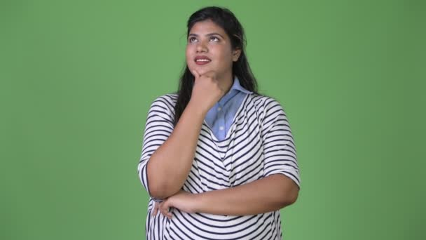 Young overweight beautiful Indian businesswoman against green background