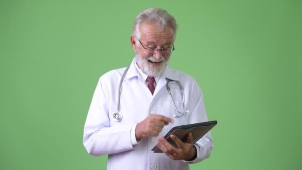 Fešák starší vousatý muž lékař na zeleném pozadí