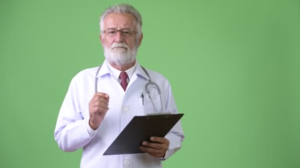 Schöner bärtiger Oberarzt vor grünem Hintergrund