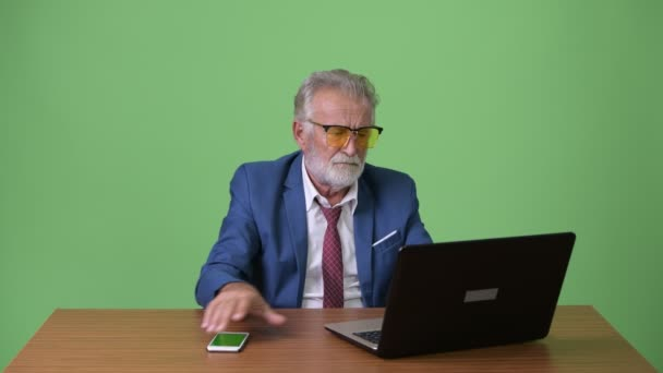 Gut aussehend senior bärtigen Geschäftsmann vor grünem Hintergrund
