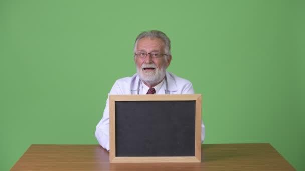Handsome senior bearded man doctor against green background