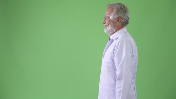 Studio shot of handsome senior bearded man doctor against chroma key with green background
