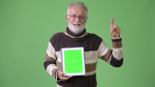 Handsome senior bearded man wearing warm clothing against green background