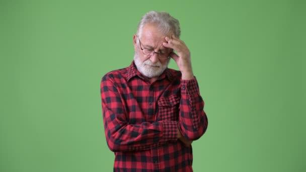 Handsome senior bearded man against green background
