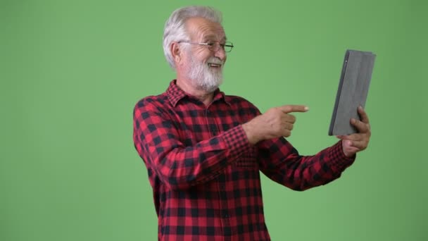 Handsome senior bearded man against green background