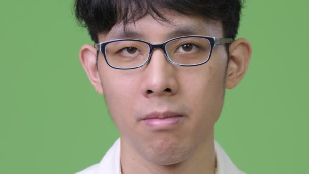 Head shot of young Asian businessman against green background