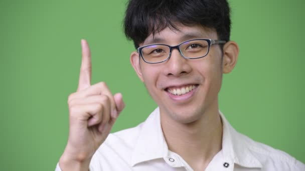 Young Asian businessman smiling while pointing up