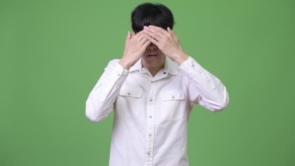 Young Asian businessman covering eyes as see no evil concept