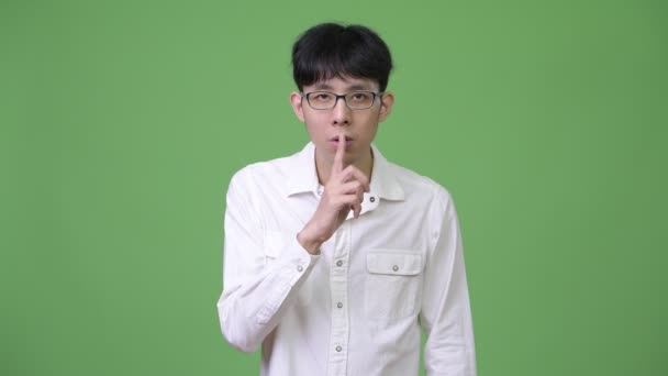 Young Asian businessman with finger on lips