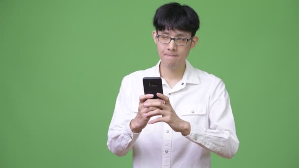 Young Asian businessman using phone and thinking