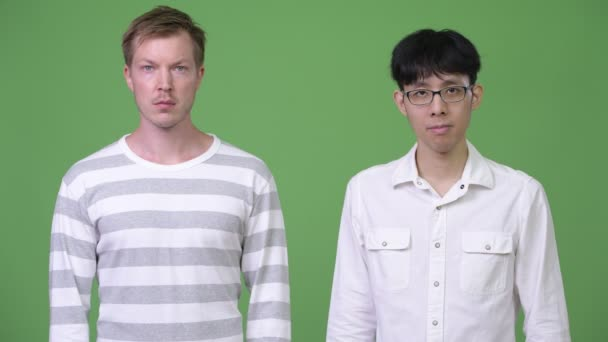 Two young multi-ethnic businessmen together against green background