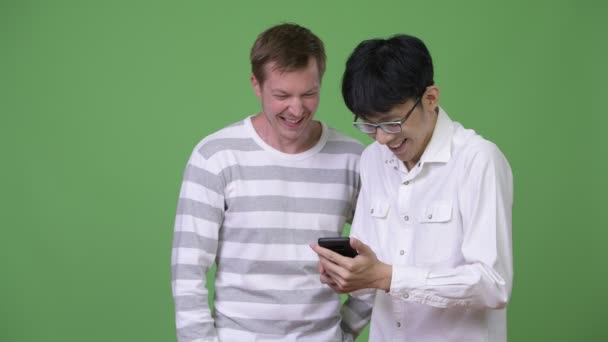 Two happy young multi-ethnic businessmen using phone together