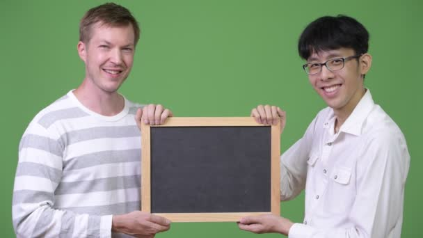 Two happy young multi-ethnic businessmen holding blackboard together
