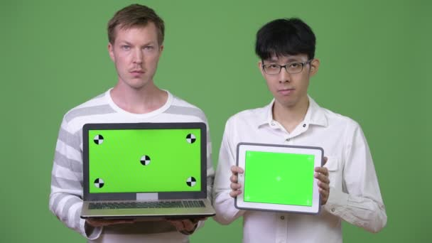 Two young multi-ethnic businessmen showing laptop and digital tablet to the camera