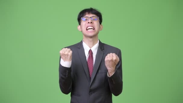 Young happy Asian businessman excited with both fists raised