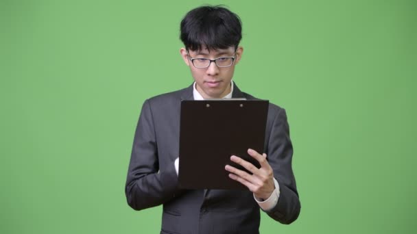 Young Asian businessman reading and thinking with clipboard