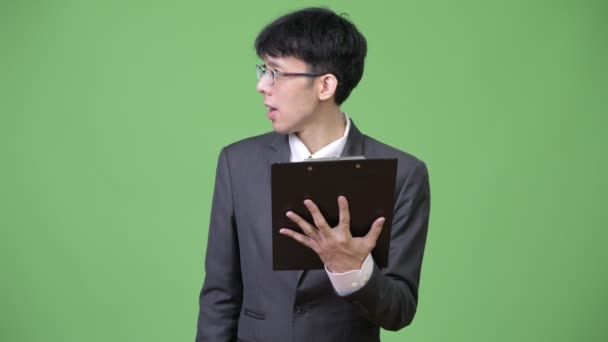 Young Asian businessman reading with clipboard and talking to the side