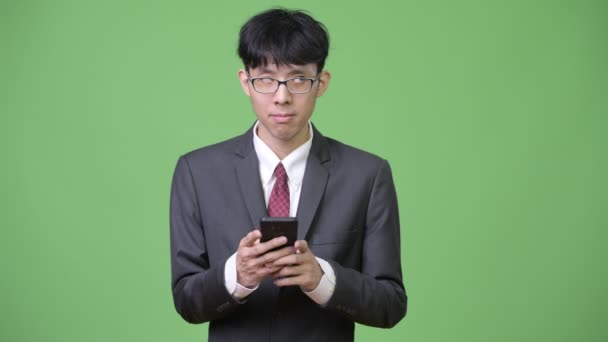 Young Asian businessman thinking while using phone