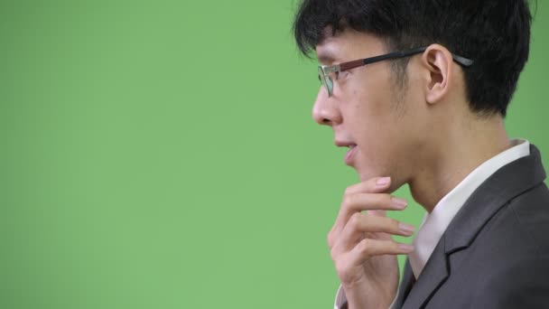 Profile view of young Asian businessman thinking