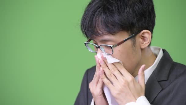 Sick young Asian businessman blowing nose on tissue