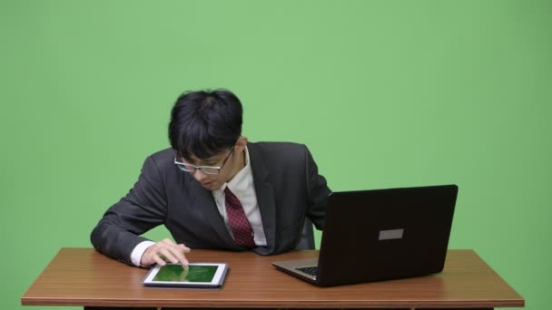 Young Asian businessman multi-tasking with laptop and tablet