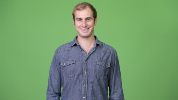 Young happy man smiling against green background