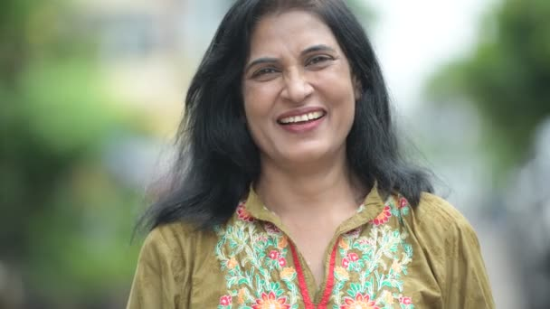Mature happy beautiful Indian woman smiling in the streets outdoors
