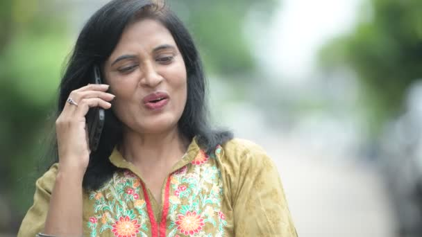 Mature happy beautiful Indian woman talking on the phone while thinking in the streets outdoors