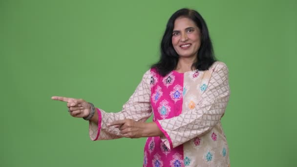 Mature happy beautiful Indian woman smiling while pointing to the side