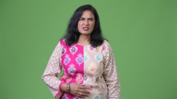 Mature stressed Indian woman having stomach ache