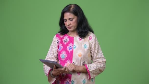 reife schöne indische Frau mit digitalem Tablet