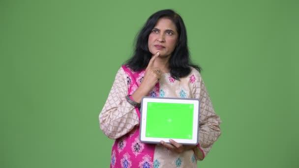 Reife schöne indische Frau denken und zeigt digital-Tablette