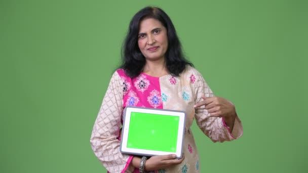 Reife schöne Inderin zeigt digital-Tablette und Zeigefinger