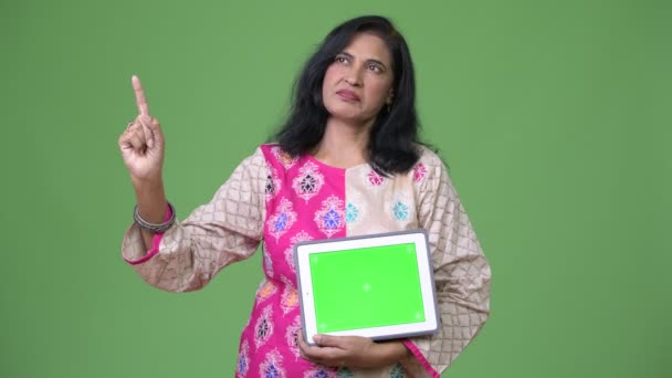 Mature beautiful Indian woman showing digital tablet and pointing finger up while thinking