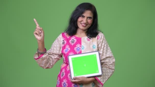 Reife glücklich schöne Inderin zeigt digital-Tablette und Finger oben