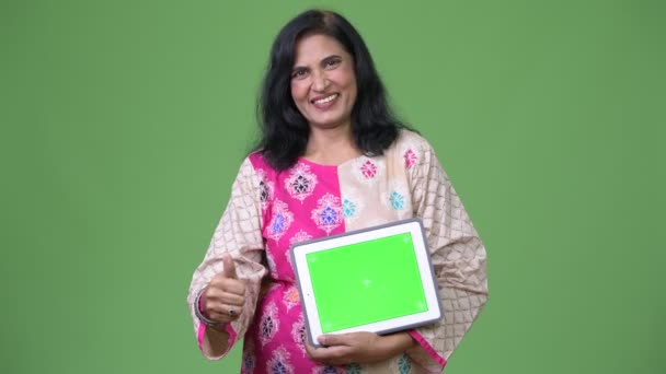 Mature happy beautiful Indian woman showing digital tablet and giving thumbs up