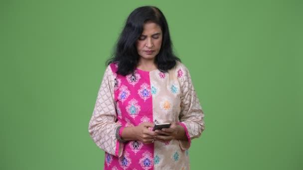 Ältere glücklich schöne indische Frau lächelt, während mit Telefon