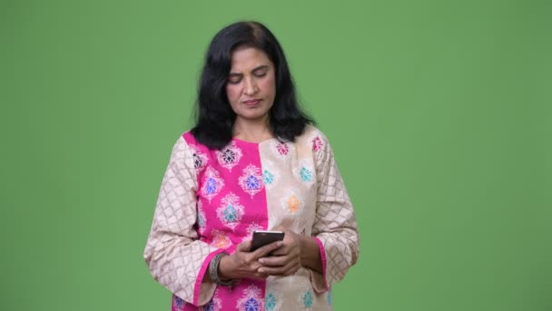 Mature happy beautiful Indian woman using phone and getting good news