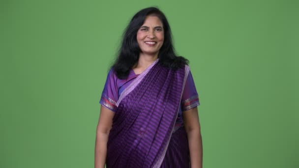 Mature happy beautiful Indian woman smiling while wearing Sari traditional clothes
