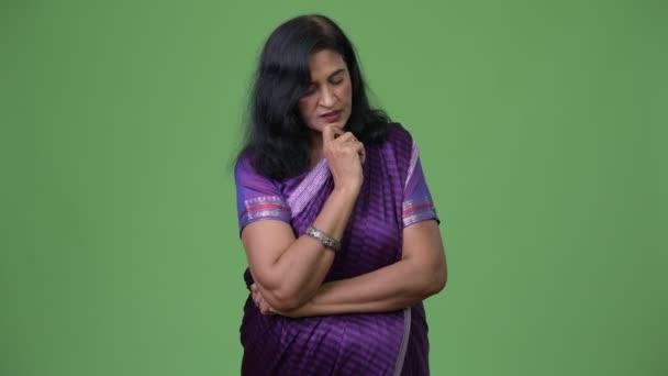 Reife betonte Indianerin denken während der Tracht Sari