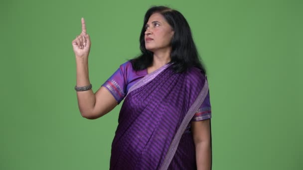 Mature beautiful Indian woman pointing up while thinking