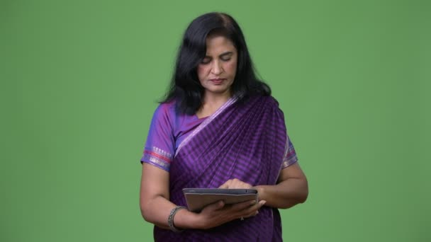 Studioaufnahme einer reifen schönen indischen Frau in traditioneller Kleidung vor Chroma-Schlüssel mit grünem Hintergrund