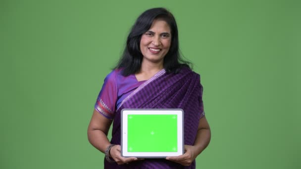 Mature happy beautiful Indian woman smiling while showing digital tablet