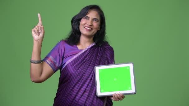 Reife glücklich schöne Inderin denken während der Vorführung digital-Tablette und Finger oben