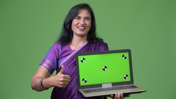 Reife glücklich schöne Inderin zeigt Laptop und Daumen aufgeben