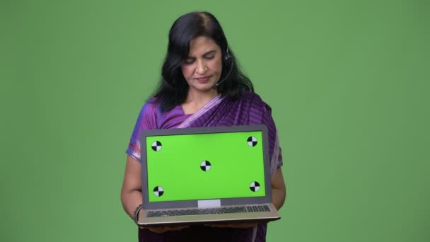 Mature beautiful Indian woman as call center representative showing laptop