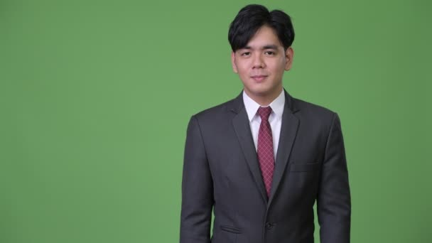 Young handsome Asian businessman showing something