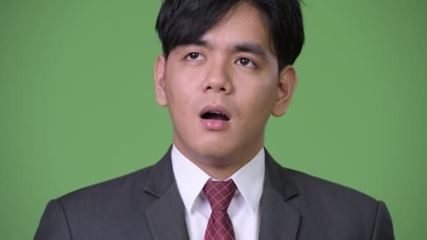 Young handsome Asian businessman looking bored