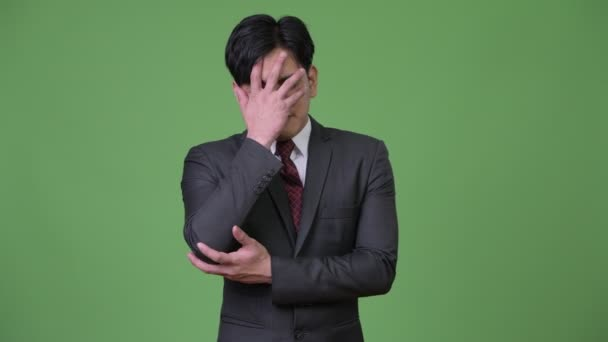 Young stressed Asian businessman getting bad news