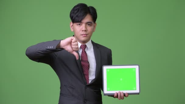 Young handsome Asian businessman using digital tablet